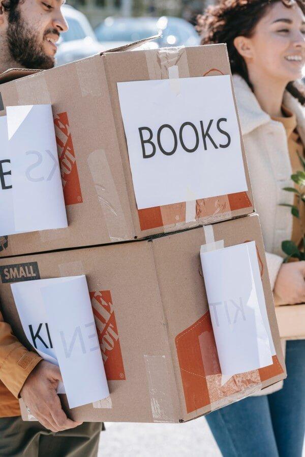 """זוג סוחב ארגזים שעליהם כתוב """"ספרים"""""""