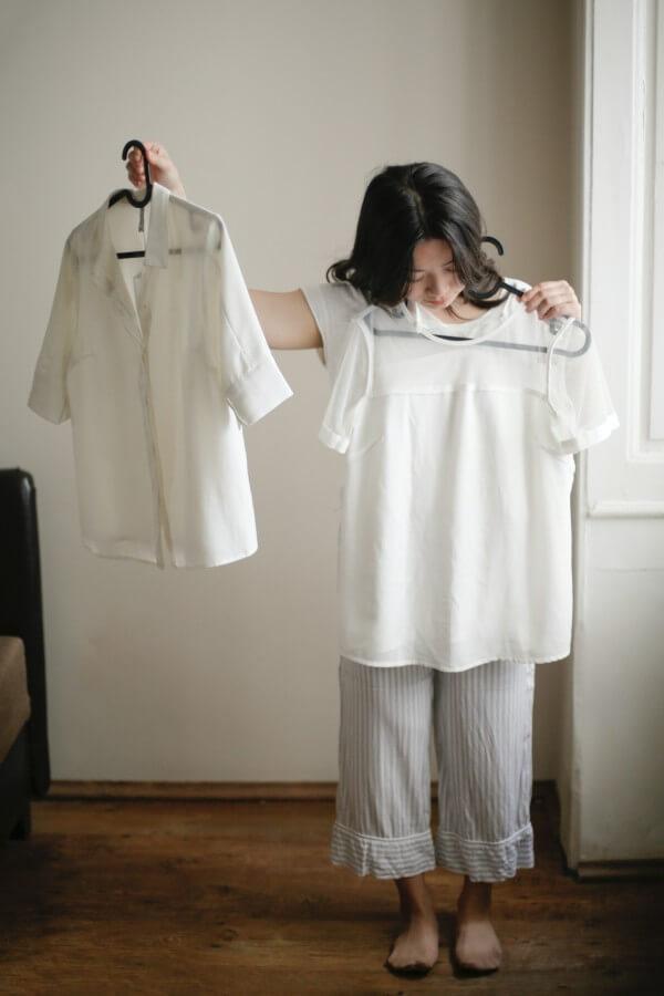 בחורה בחנות בגדים, מתלבטת בין שתי חולצות.