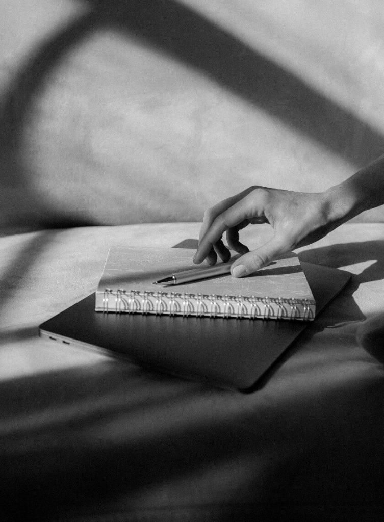 מחשב נייד, עליו מחברת, עליה עט, ומעל יד שמניחה את העט