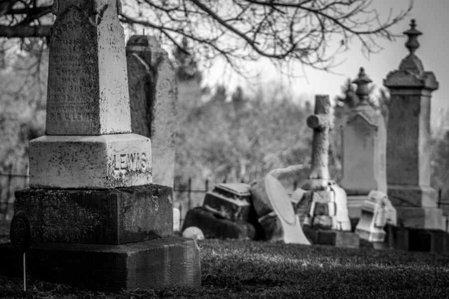 תמונת שחור לבן של מצבות בבית קברות עתיק, חלקן נפולות.